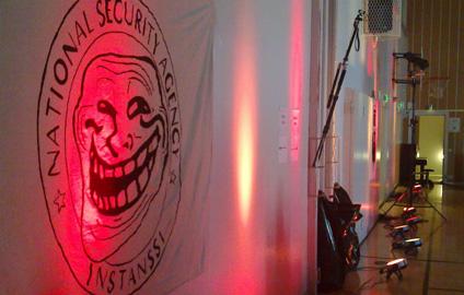 kuvituskuva Instanssi 2014 -tapahtumasta. Seinällä National Security Agency Instanssi -logo, jonka keskellä on trollface. Valot osoittavat seinälle punaisina ja keltaisina